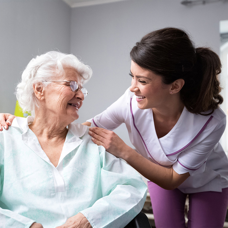 Nurse with a happy elderly woman seated