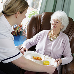 caregiver serving a female resident a tray of food