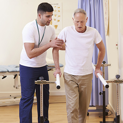 Therapist assisting a resident using parallel walking bars